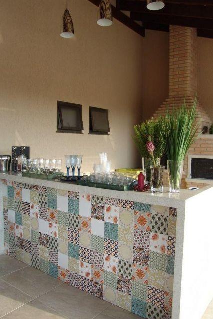 Bancada de uma área de churrasqueira feita com azulejos portugueses de diferentes tipos e cores.