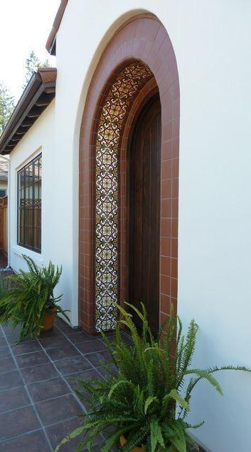Entrada de uma casa em formato de arco com sua parte interna revestida com azulejos portugueses.