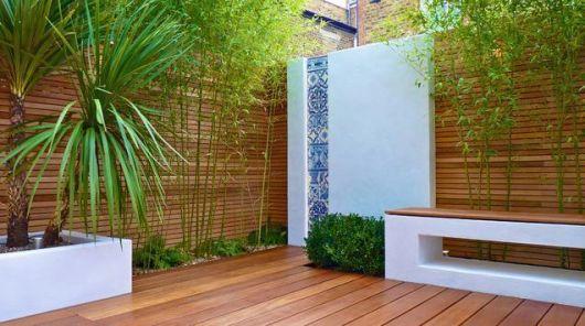 Jardim com chão e paredes de madeira. Dentro dele há uma parede lisa com uma faixa vertical feita com azulejos portugueses.