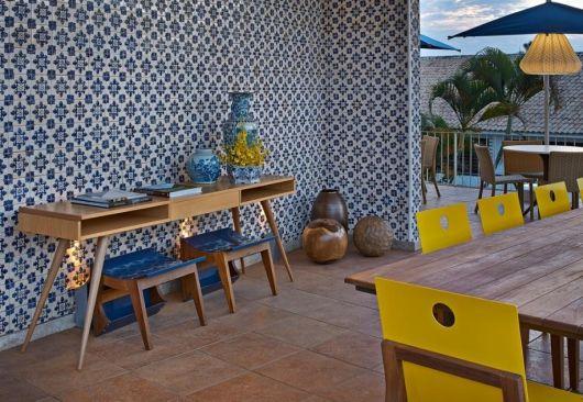 Parede de uma área externa com diversas mesas revestida completamente com azulejos portugueses.