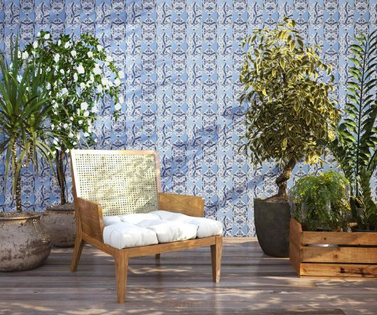 Área verde de um jardim com uma poltrona simples. Atrás dela há uma parede revestida completamente com azulejos portugueses.