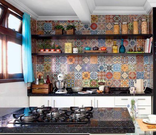Foto da bancada de uma cozinha com a parede atrás dela revestida completamente com azulejos portugueses coloridos, um diferente do outro.