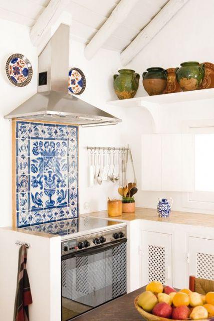 Quadro feito de azulejos portugueses posicionado entre o fogão e o exaustor da cozinha.