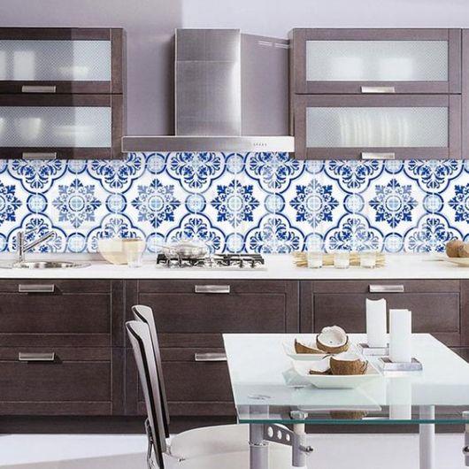Bancada de uma cozinha com diversas gavetas em frente a uma parede revestida completamente com azulejos portugueses baseados em formas geométricas.