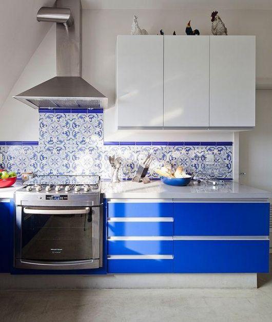 Faixa de revestimento na parede da bancada da cozinha feita com azulejos portugueses. Ela é um pouco mais alta na área entre o fogão e o exaustor.