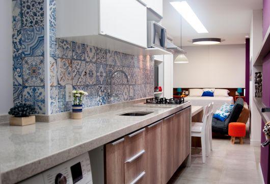 Foto tirada lateralmente da bancada de uma cozinha ligada diretamente à sala. A parede atrás da torneira é saliente e revestida com azulejos portugueses.