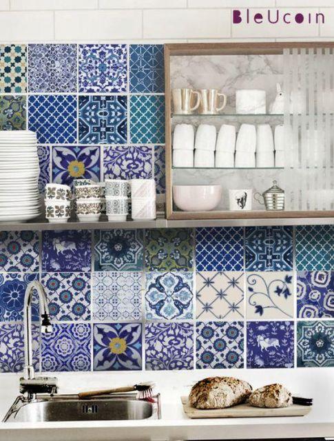 Foto de uma parede de cozinha revestida com azulejos portugueses de diferentes tipos. Nela há uma estante onde estão posicionadas as louças, algumas com estampas que lembram azulejos portugueses.
