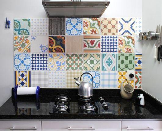 Azulejos portugueses coloridos de diferentes tipos posicionados entre o fogão e o exaustor.