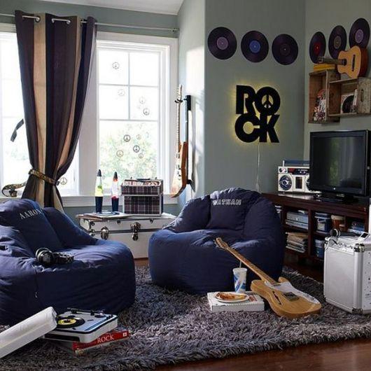 """Sala de uma casa com dois puffs próximos a uma estante de televisão com discos de vinil, instrumentos musicais e um letreiro escrito """"Rock"""" na parede."""