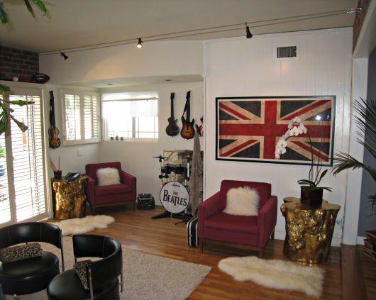 Sala de estar com duas poltronas, uma bateria do The Beatles, guitarras elétricas penduradas na parede e um quadro grande com a bandeira do Reino Unido.