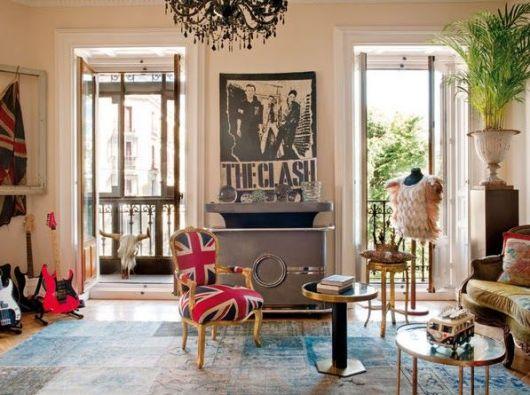 Sala de estar com guitarras em um dos cantos, uma poltrona personalizada com a bandeira do Reino Unido e um quadro grande no centro do The Clash.