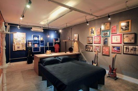 Quarto com bastante espaço onde há duas guitarras ao lado da cama e uma parede cheia de quadros com bandas de rock.