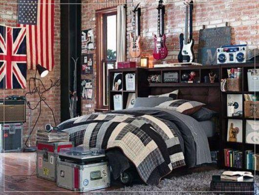 Quarto com paredes de tijolos onde há uma bandeira do Reino Unido ao lado de uma bandeira dos Estados Unidos. Além disso, guitarras e quadros também estão pendurados na parede. Na cabeceira da cama há diversos discos de vinil e no chão estão caixas de som.