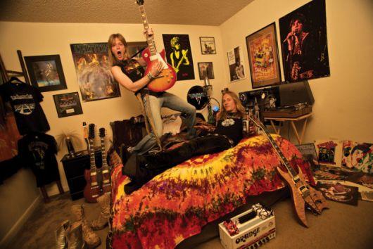 Casal em um quarto com decoração rock. Na parede há diversos posteres de bandas de rock famosas e diversos instrumentos estão posicionados no chão.