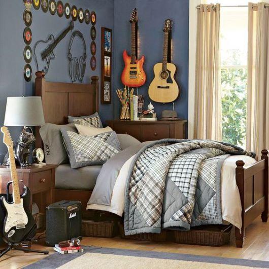 Foto de um quarto com uma guitarra e uma caixa de som posicionadas ao lado da cama. Acima dela, há diversos discos de vinil pendurados e uma guitarra elétrica ao lado de um violão, ambos também pendurados.