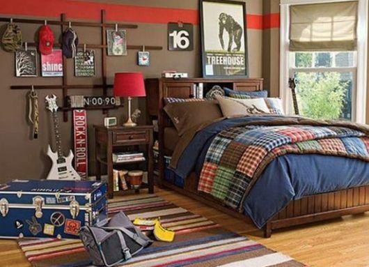 Foto de um quarto com duas guitarras e uma caixa de carregar aparatos de música no chão.