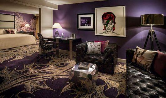 Quarto ligado à uma pequena área de lazer onde há poltronas com almofadas no The Doors e um quadro grande de David Bowie no centro da parede.