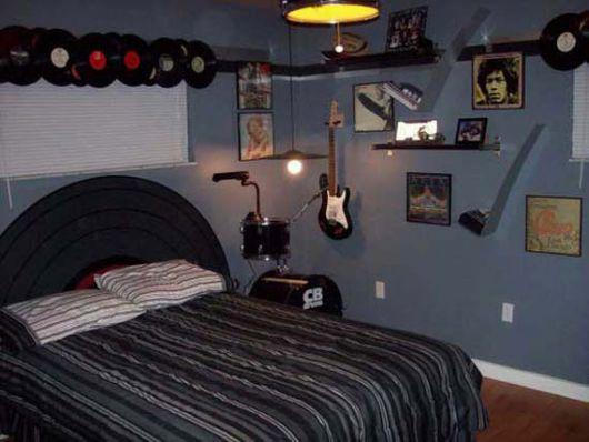Foto de um quarto com a cabeceira da cama similar a um disco de vinil. Na parede há diversos discos de vinil, instrumentos musicais e quadros de ícones do rock.