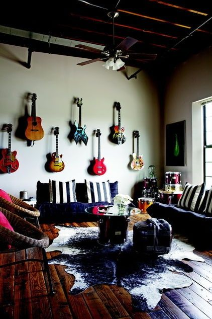 Sala de estar com uma mesa de centro cuja base é uma parte de bateria e a parede tem vários instrumentos musicais pendurados.