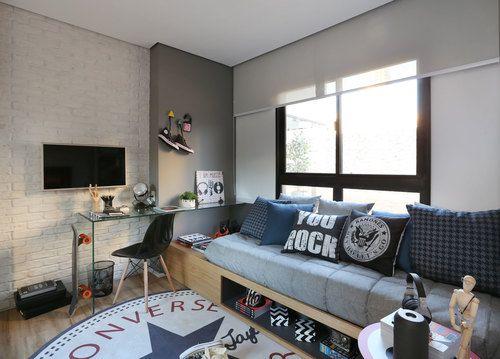 Sala de estar com um sofá repleto de almofadas que fazem referências ao rock e um tapete da All Star Converse.