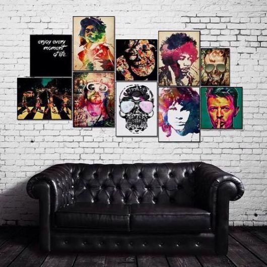 Sofá de uma sala de estar posicionado em frente a uma parede de tijolos repleta de quadros com ícones do rock como David Bowie, Jimi Hendrix e The Beatles.