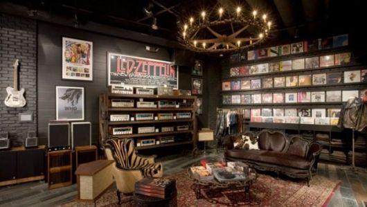 Sala de estar ampla com quadros de bandas de parede e uma estante cheia de discos de vinil.