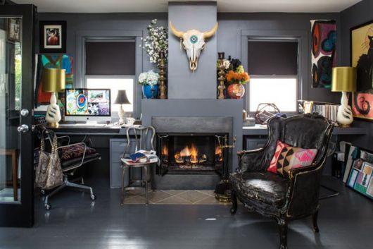 Sala de estar com lareira no centro e uma poltrona. Na parede lateral há uma estante que comporta diversos discos de vinil.