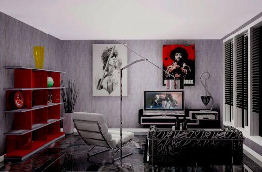 Sala de estar com uma televisão ligada transmitindo um clipe do Guns n Roses e na parede há quadros de outras bandas de rock.