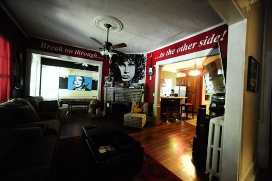 "Sala de estar ampla com instrumentos musicais dispostos ao longo de sua extensão e paredes personalizadas com um quadro do The Doors e os dizeres ""Break on through the other side!"""