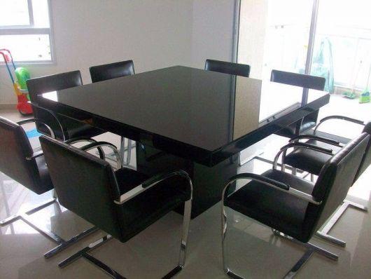 Mesa de jantar preta laqueada.