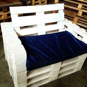 Poltrona de pallet pintada de branco com uma base horizontal muito sólida e uma acolchoado azul no assento.