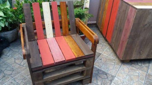 Poltrona de pallets com madeiras pintadas de diversas cores diferentes.
