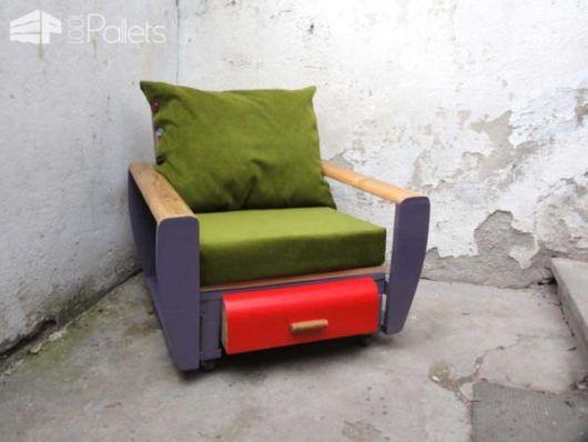 Poltrona de pallet colorida com acolchoados e uma gaveta abaixo do assento.
