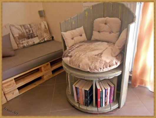 Poltrona de pallet acolchoada com formato arredondado e suporte para livros abaixo do assento.