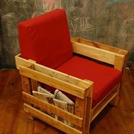 Poltrone de pallet com um suporte para jornal na lateral e acolchoado no assento e na parte de que dá suporte às costas.