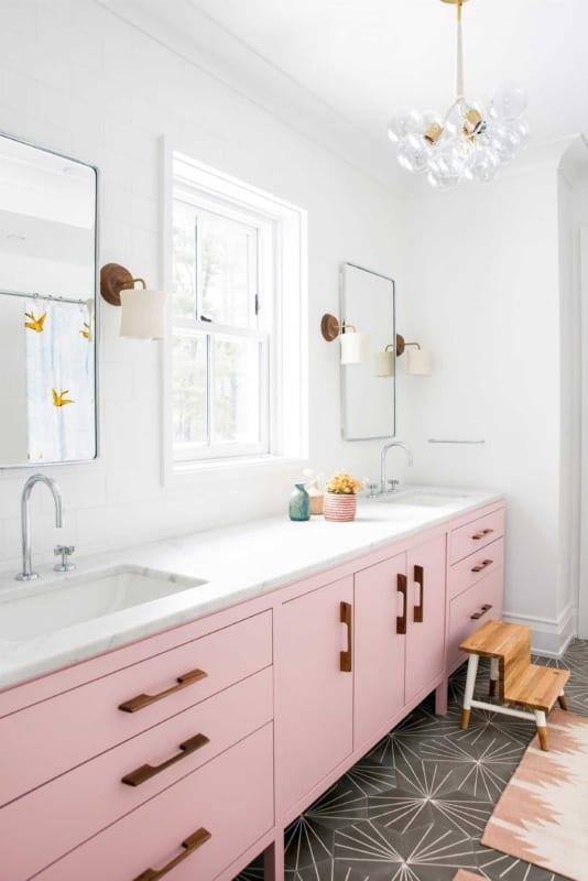 Banheiro branco com armário rosa e pendente de lampadas 1