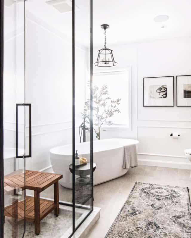 Banheiro branco com banheira e luminária pendente