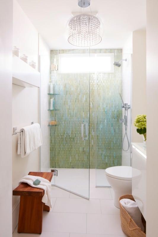 Banheiro branco e verde com lustre pendente de cristal
