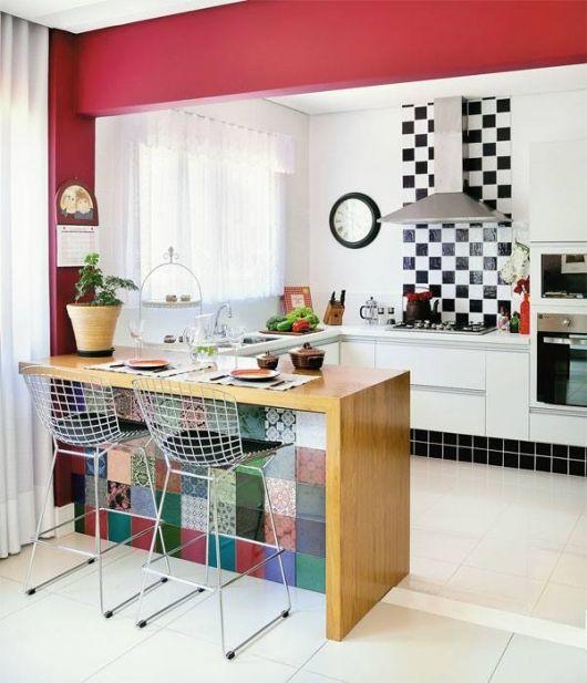 Cozinha branca com rosa e azulejos coloridos.