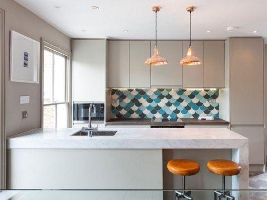 Cozinha branca com banquetas redondas e adesivo de parede.