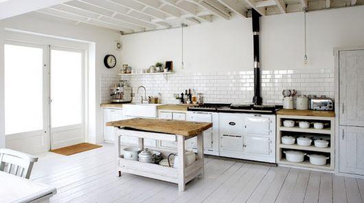 Cozinha clean com mesa de madeira.