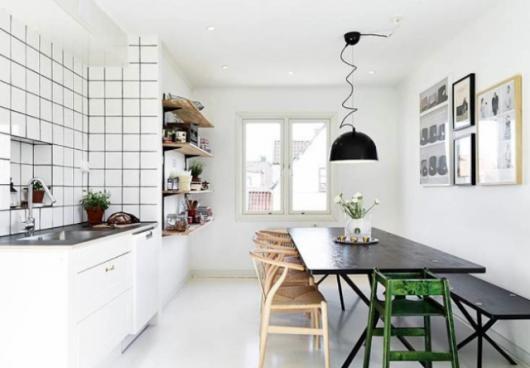 Cozinha branca com mesa de madeira preta e azulejos brancos.