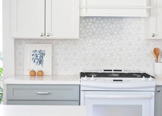 Cozinha clean com armários em branco e azulejos de parede na mesma cor.
