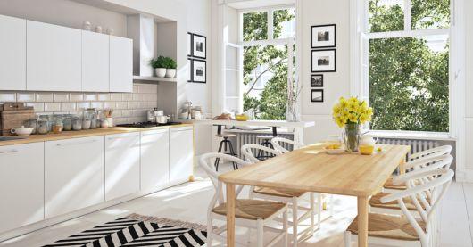 Cozinha branca com mesa de madeira amarela.