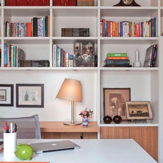 Foto de uma mesa com um notebook fechado sobre ela. Atrás da mesa há uma estante em MDF com quadros e livros.