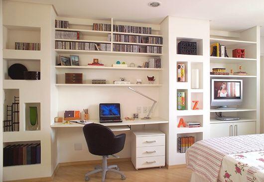 Foto de um quarto onde há uma parede totalmente voltada para Home Office.  Nela há uma cadeira em frente a um notebook e diversas estantes paralelas acima contendo objetos de escritório e decoração.