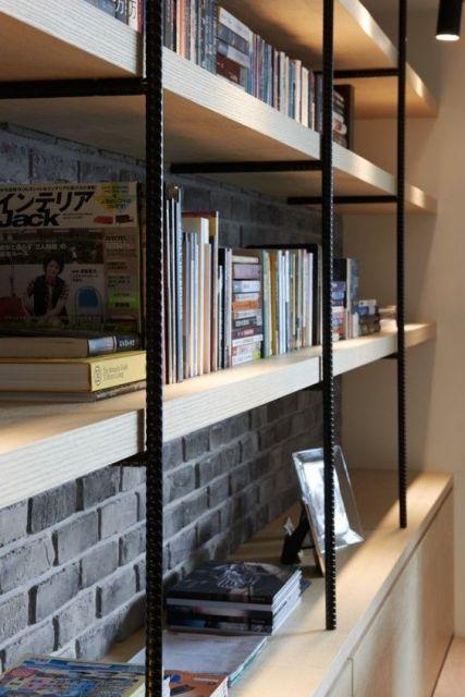 Foto de uma estante com vigas de ferro aparentes e bases de madeira onde estão posicionados livros e quadros.  Ela vai de uma extremidade lateral da parede à outra.