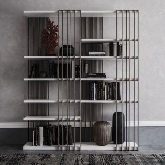 Foto de uma estante com vigas de aço aparente e bases paralelas onde estão posicionados livros e objetos de decoração.