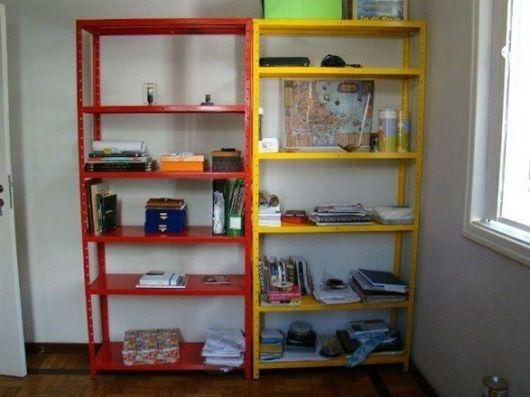 Duas estantes de escritório em aço posicionadas uma ao lado da outra. Elas são cada uma de cor diferente e têm cinco andares cada uma.