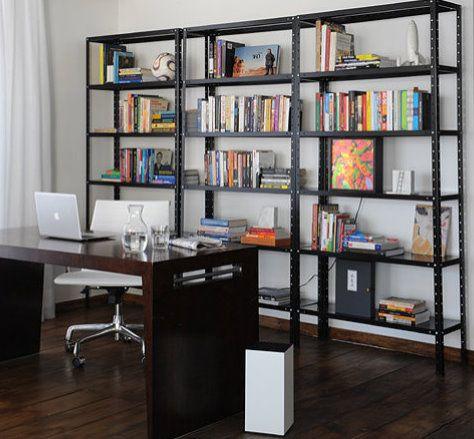 Foto de uma mesa em madeira com um notebook sobre ela. Na parede ao fundo há uma estante de ferro grande que suporta diversos livros e alguns objetos de decoração.